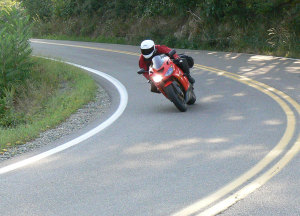 Body position helps drop the bike into the turn while requiring less lean angle.